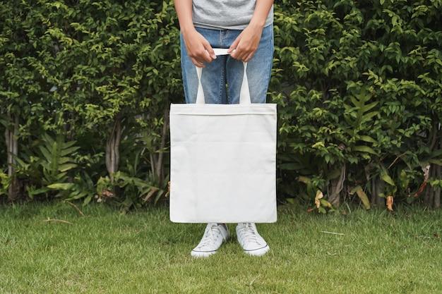 Femme hipster avec un sac en coton blanc sur fond de feuille verte