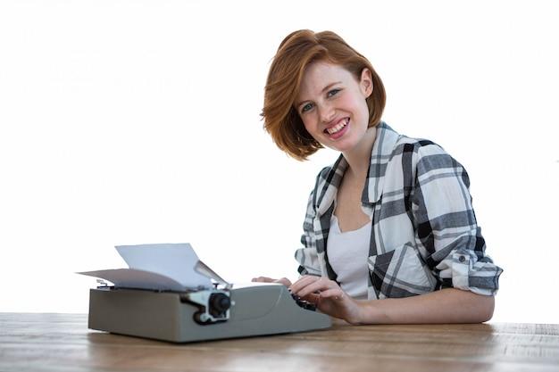 Femme hipster souriante assise à un bureau, tapant sur sa machine à écrire