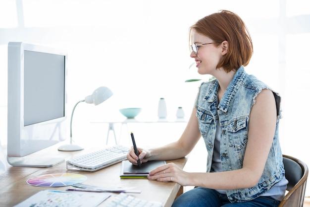 Femme hipster souriante à un bureau écrit sur sa tablette