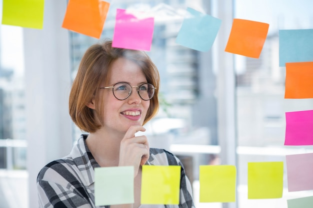Femme hipster souriante dans son bureau, collant des notes à un mur