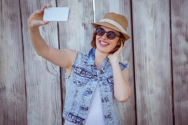 Femme hipster souriante prenant un selfie