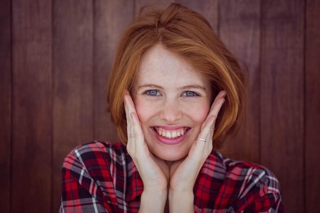 Femme hipster souriante avec ses mains sur son visage