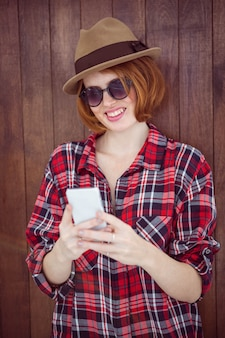 Femme hipster souriante sur son smartphone