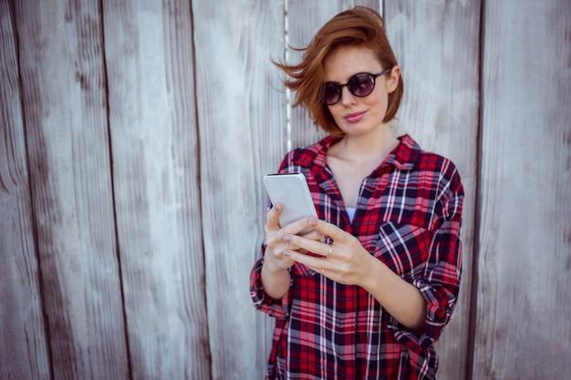 Femme hipster souriante sur son smartphone