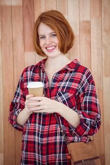 Femme hipster souriante tenant une tasse de café