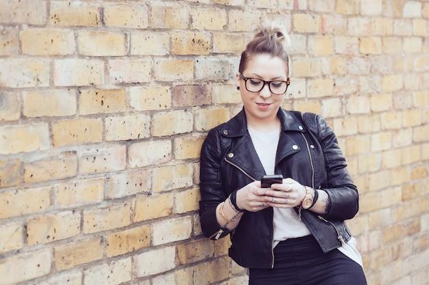 Femme hipster en tapant sur un téléphone intelligent à londres.