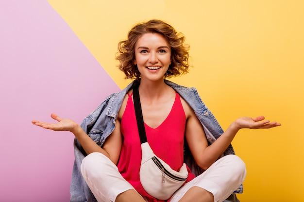 Femme de hipster avec visage surprise qui pose en studio sur rose et jaune.