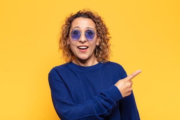 Femme hispanique d'âge moyen à l'air excité et surpris pointant vers le côté et vers le haut pour copier l'espace