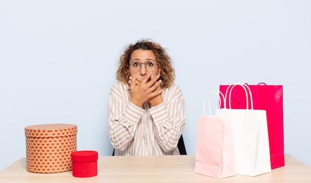 Femme hispanique d'âge moyen couvrant la bouche avec les mains avec une expression choquée et surprise, gardant un secret ou disant oups