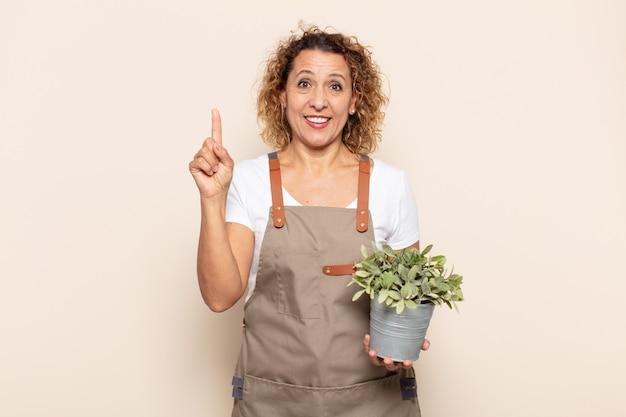 Femme hispanique d'âge moyen se sentant comme un génie heureux et excité après avoir réalisé une idée, levant joyeusement le doigt, eurêka!