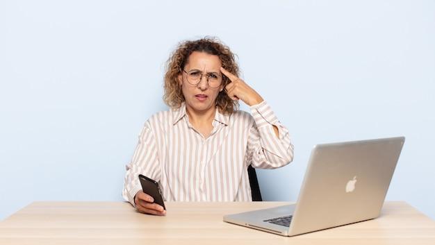 Femme hispanique d'âge moyen se sentant confuse et perplexe, montrant que vous êtes folle, folle ou folle