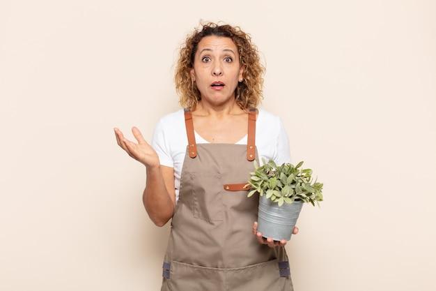 Femme hispanique d'âge moyen se sentant extrêmement choquée et surprise, anxieuse et paniquée, avec un regard stressé et horrifié