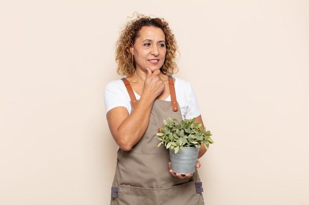 Femme hispanique d'âge moyen souriant avec une expression heureuse et confiante avec la main sur le menton