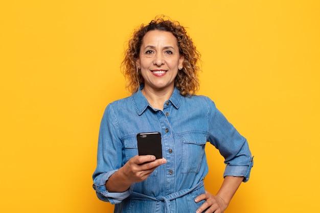 Femme hispanique d'âge moyen souriant joyeusement avec une main sur la hanche et une attitude confiante, positive, fière et amicale