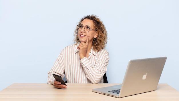 Femme hispanique d'âge moyen souriant joyeusement et rêvant ou doutant, regardant sur le côté