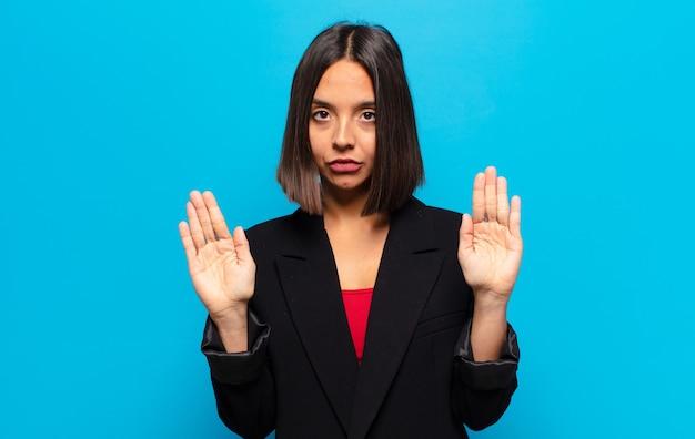 Femme hispanique à l'air sérieuse, malheureuse, en colère et mécontente interdisant l'entrée ou disant stop avec les deux paumes ouvertes