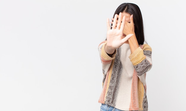 Femme hispanique assez mince couvrant le visage avec la main