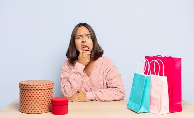 Femme hispanique avec la bouche et les yeux grands ouverts et la main sur le menton, se sentant désagréablement choquée, disant quoi ou wow