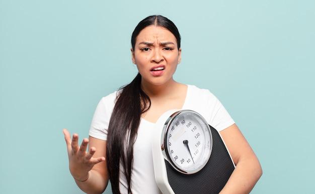 Femme hispanique à la colère, agacée et frustrée hurlant wtf ou quel est le problème avec vous