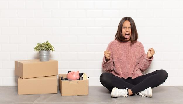 Femme hispanique criant agressivement avec une expression de colère ou avec les poings serrés célébrant le succès