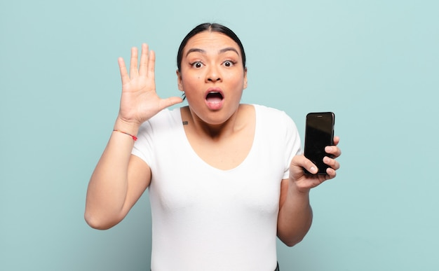 Femme hispanique criant avec les mains en l'air, se sentant furieuse, frustrée, stressée et bouleversée