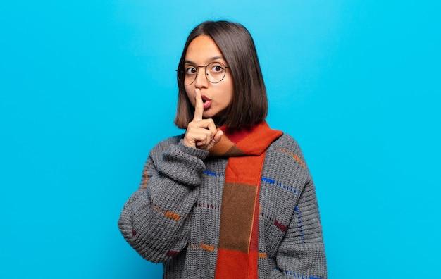 Femme hispanique demandant le silence et la tranquillité, faisant des gestes avec le doigt devant la bouche, disant chut ou gardant un secret
