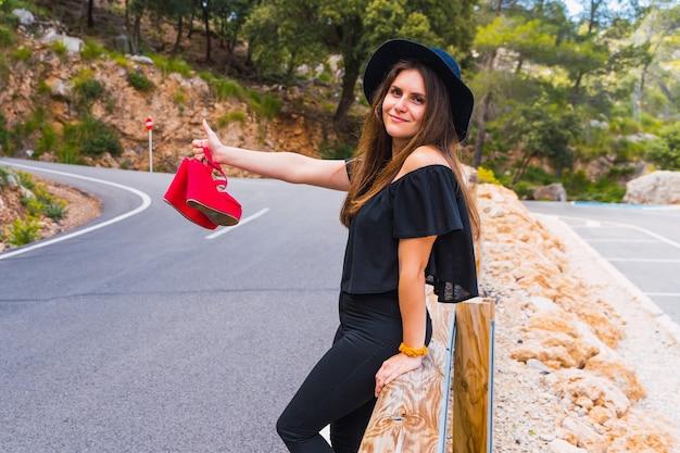 Femme hispanique faisant de l'auto-stop sur la route et souriant