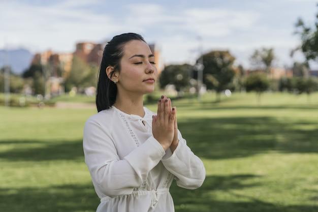 Femme hispanique faisant du yoga dans un parc