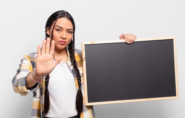 Femme hispanique à la grave, sévère, mécontente et en colère montrant la paume ouverte faisant le geste d'arrêt