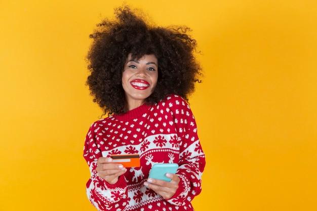 Femme hispanique, latina, carte de crédit de noël et smartphone