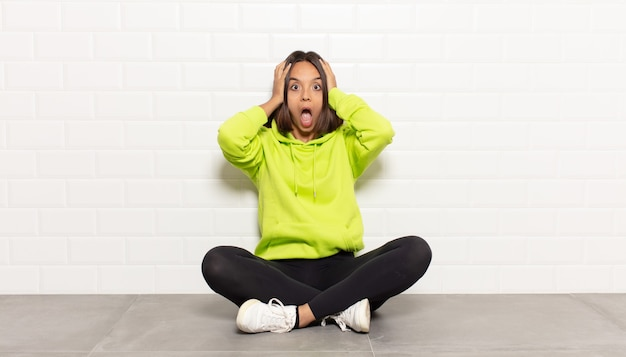 Femme hispanique levant les mains à la tête, bouche bée, se sentant extrêmement chanceux, surpris, excité et heureux