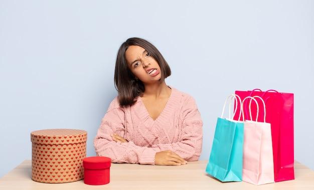 Femme hispanique perplexe et confuse, avec une expression stupide et stupéfaite en regardant quelque chose d'inattendu