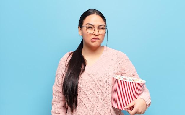 Femme hispanique à la perplexité et à la confusion, mordant la lèvre avec un geste nerveux, ne sachant pas la réponse au problème