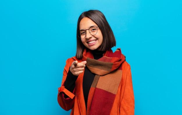 Femme hispanique pointant vers la caméra avec un sourire satisfait, confiant et amical, vous choisissant