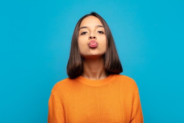 Femme hispanique pressant les lèvres avec une expression mignonne, amusante, heureuse et charmante, envoyant un baiser