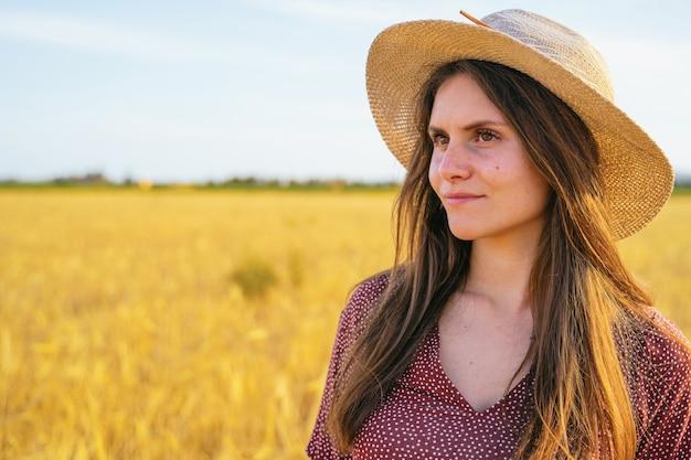 Femme hispanique profitant du coucher de soleil dans un champ de blé