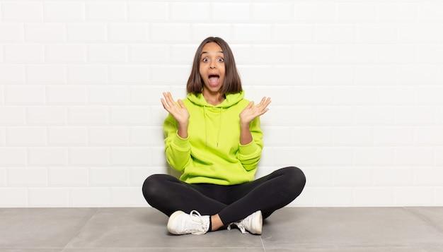 Femme hispanique se sentant choquée et excitée, riant, étonnée et heureuse à cause d'une surprise inattendue