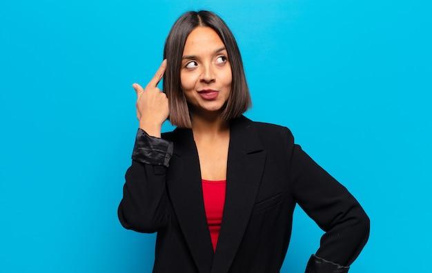 Femme hispanique se sentant confuse ou doutant, se concentrant sur une idée, réfléchissant fort, cherchant à copier l'espace sur le côté