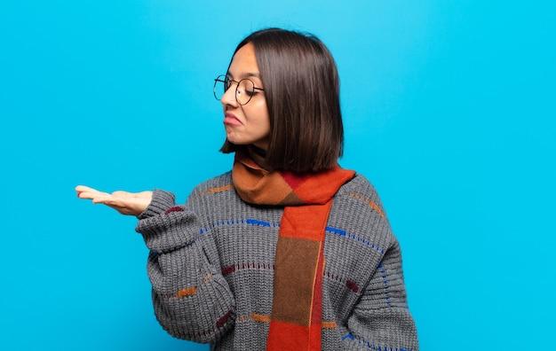 Femme hispanique se sentant heureuse et souriante avec désinvolture, à la recherche d'un objet ou d'un concept tenu sur la main sur le côté