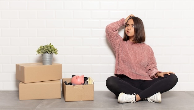 Femme hispanique se sentant perplexe et confuse, se grattant la tête et regardant sur le côté