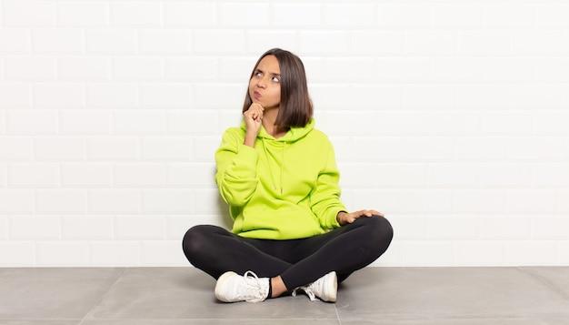 Femme hispanique se sentant réfléchie, se demandant ou imaginant des idées, rêvant et levant les yeux pour copier l'espace