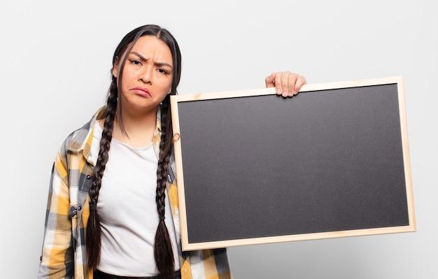 Femme hispanique se sentant triste et pleurnicharde avec un regard malheureux, pleurant avec une attitude négative et frustrée