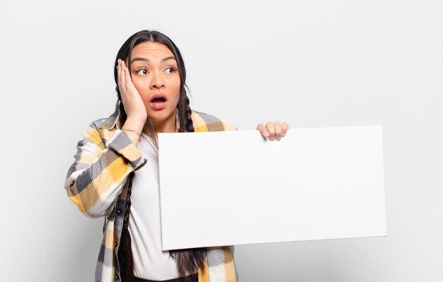 Femme hispanique se sentir heureuse, excitée et surprise, regardant sur le côté avec les deux mains sur le visage