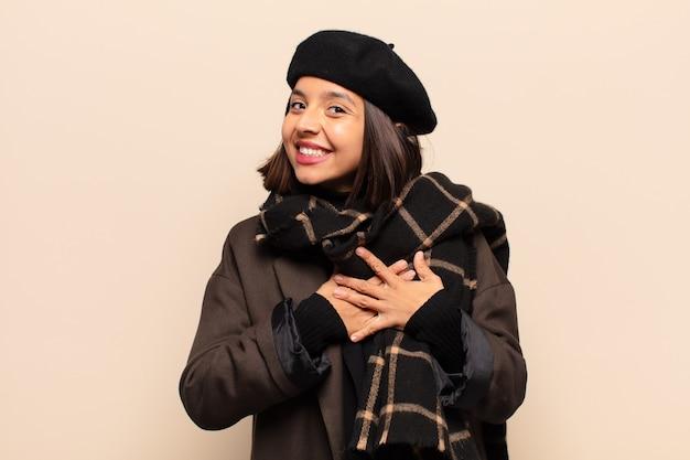 Femme hispanique se sentir romantique, heureuse et amoureuse, souriant joyeusement et se tenant la main près du cœur