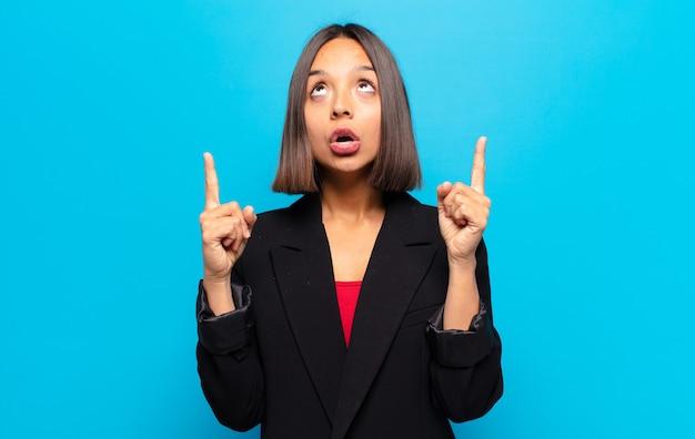 Femme hispanique semblant choquée, étonnée et bouche ouverte, pointant vers le haut avec les deux mains pour copier l'espace