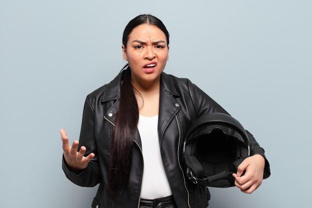 Femme hispanique semblant en colère, agacée et frustrée en criant wtf ou ce qui ne va pas avec vous
