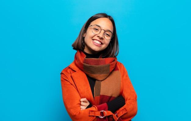 Femme hispanique souriant à la caméra avec les bras croisés et une expression heureuse, confiante et satisfaite, vue latérale
