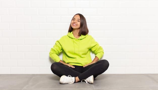 Femme hispanique souriant gaiement et avec désinvolture avec une expression positive, heureuse, confiante et détendue