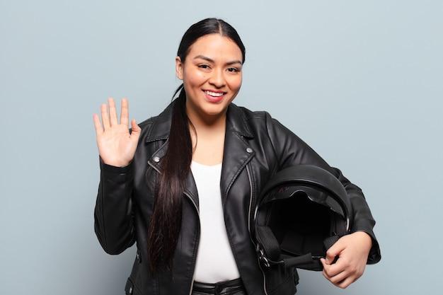 Femme hispanique souriant joyeusement et joyeusement, agitant la main, vous accueillant et vous saluant, ou vous disant au revoir