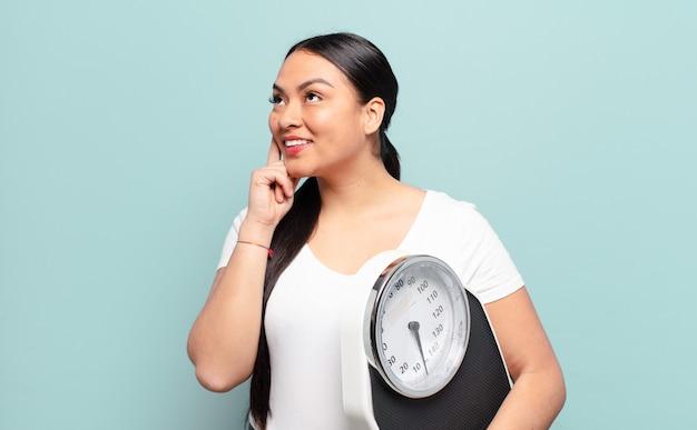 Femme hispanique souriant joyeusement et rêvant ou doutant, regardant sur le côté